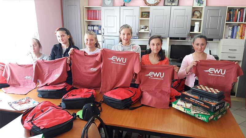 School children holding CWU shirts