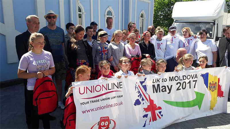 Group of volunteers and school children holding a CWUHA banner