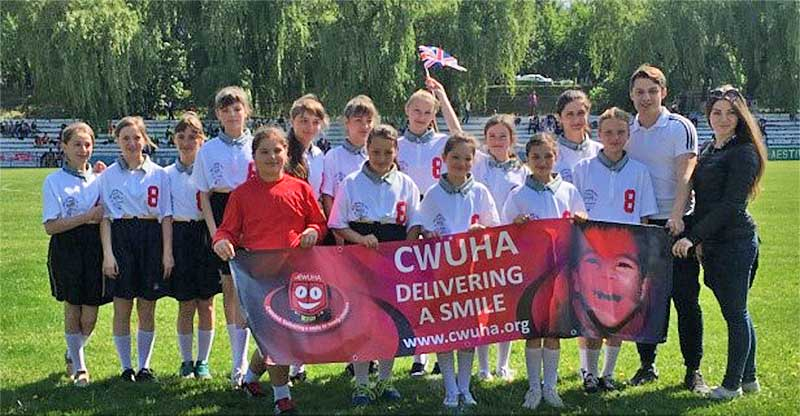 Group of school children holding a CWUHA banner