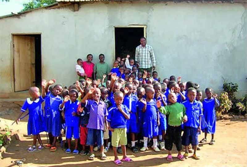 School children and staff in Africa stood outside