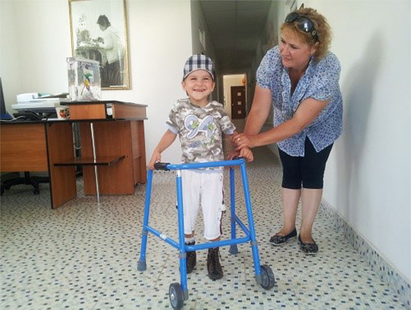 CWUHA volunteer with a child, using a walker